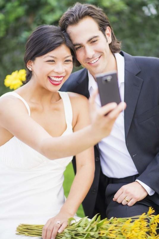 Newlywed couple taking self-portrait at wedding reception
